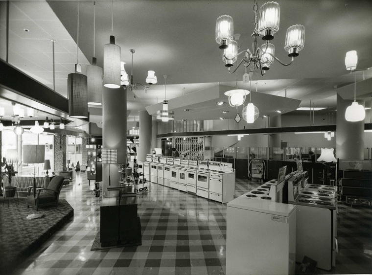Black and white photograph of an industry exhibition/fair featuring three electric stoves and promoting electric cooking. 'Bring luxury to your kitchen with electric cooking'. Collection of photographic prints made by Wm. E. Toms between 1948 - 1972 at Eastbourne Studios. Collection gifted by Mrs. Valerie M. Blennerhasset (nee Toms).